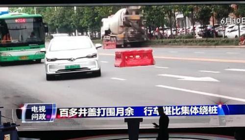 武汉一道路3站路百余井盖打围 通行车辆集体绕桩